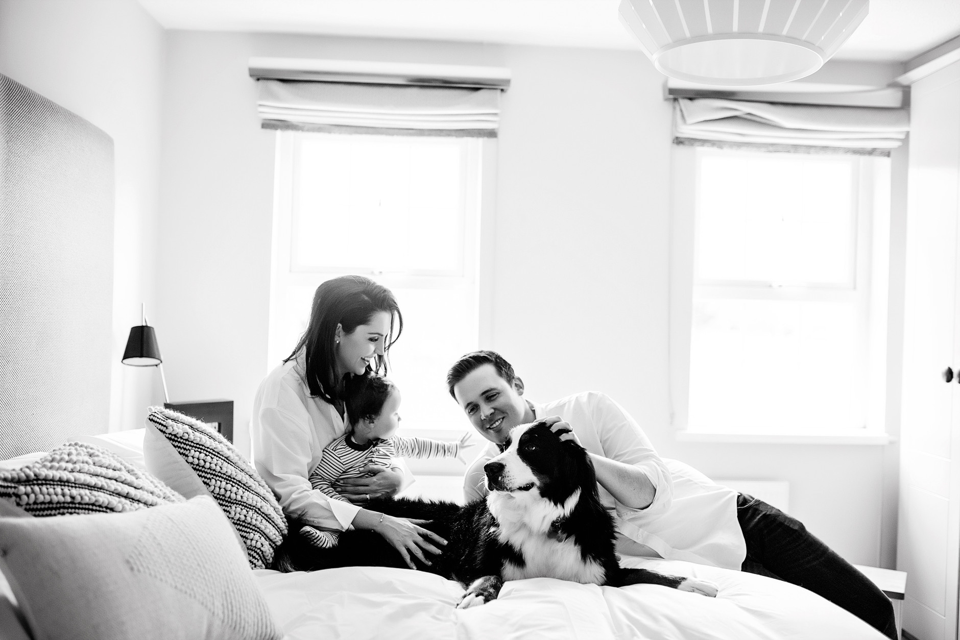 Whole family on the bed for a portrait, including a big dog