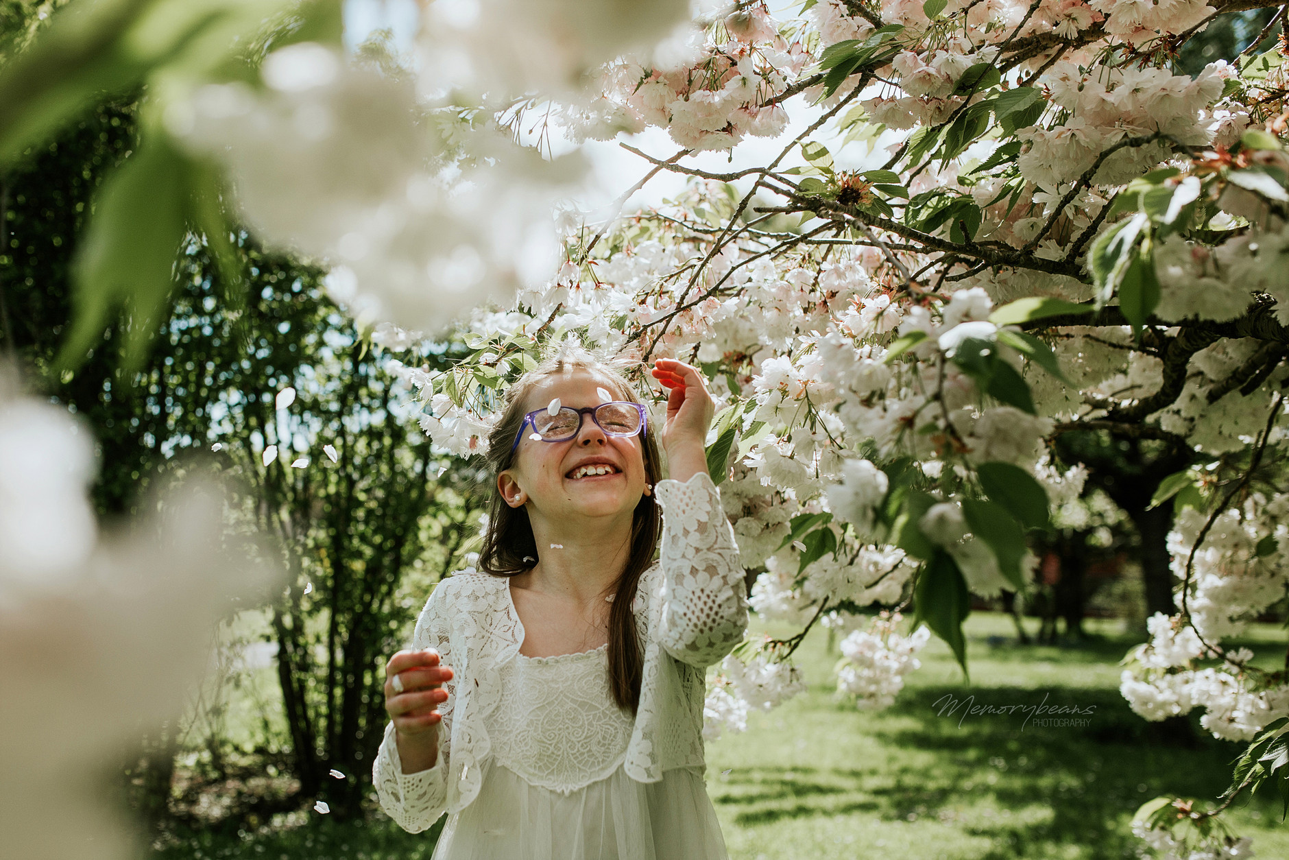 Excited first communion child under blossom trees at the Botanical Gardens in Dublin