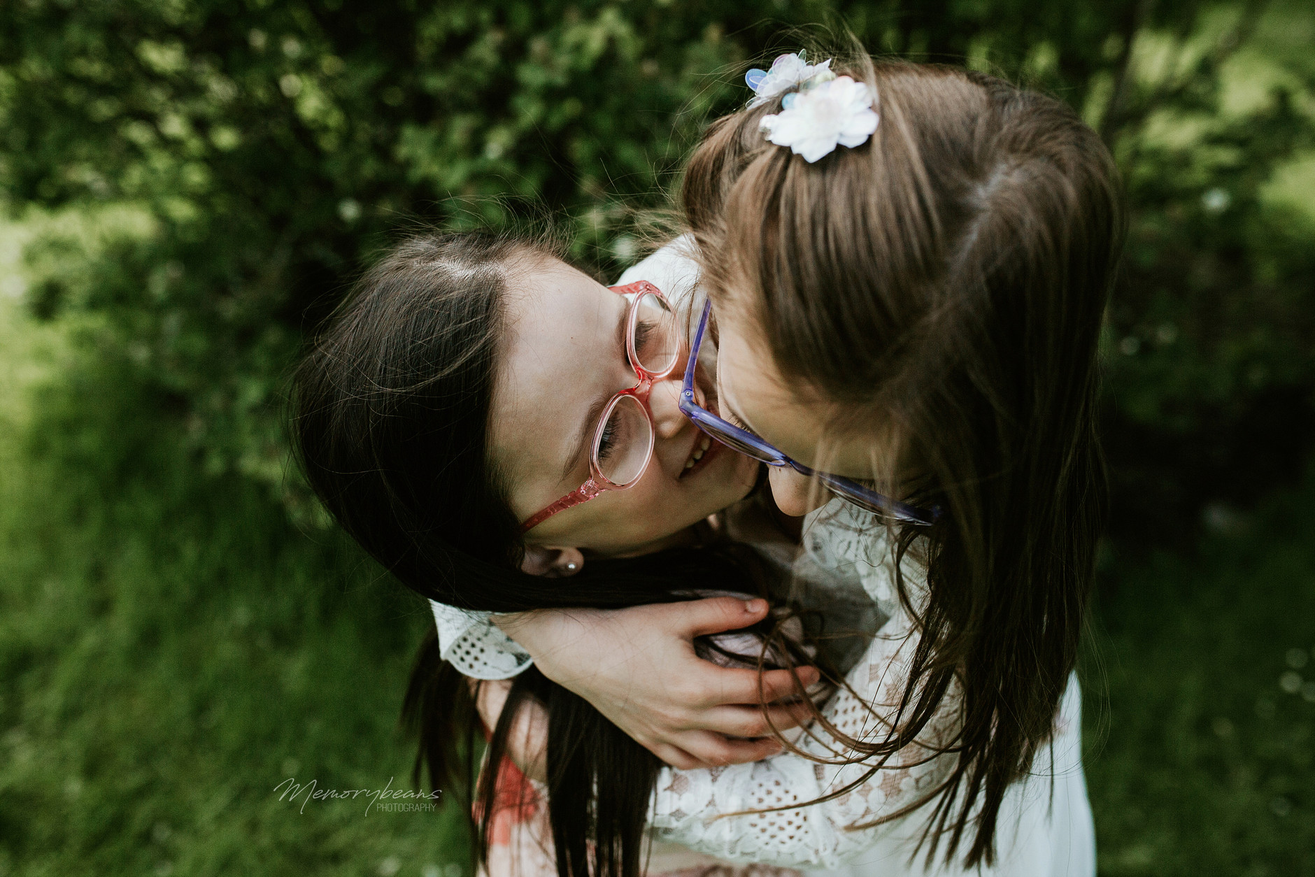First communion photos, two sisters hugging and laughing