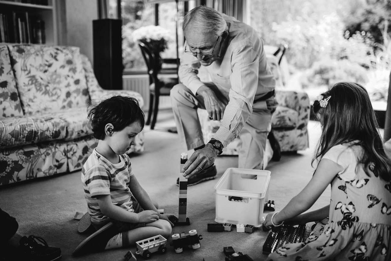 Grandfather playing lego with his grandchildren on the floor of their home in Dublin