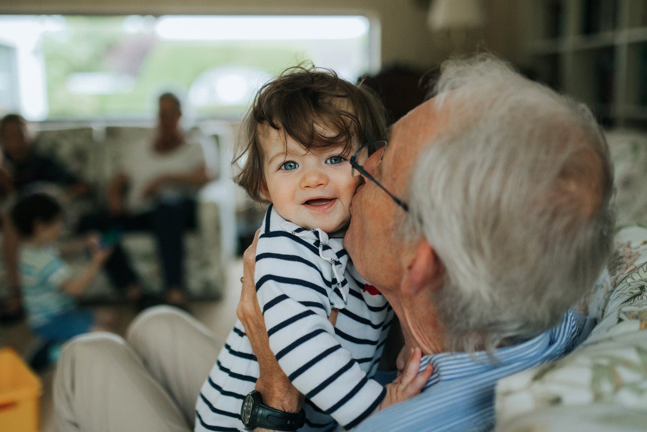 Grandfather kissing his smiling grandson on the cheek