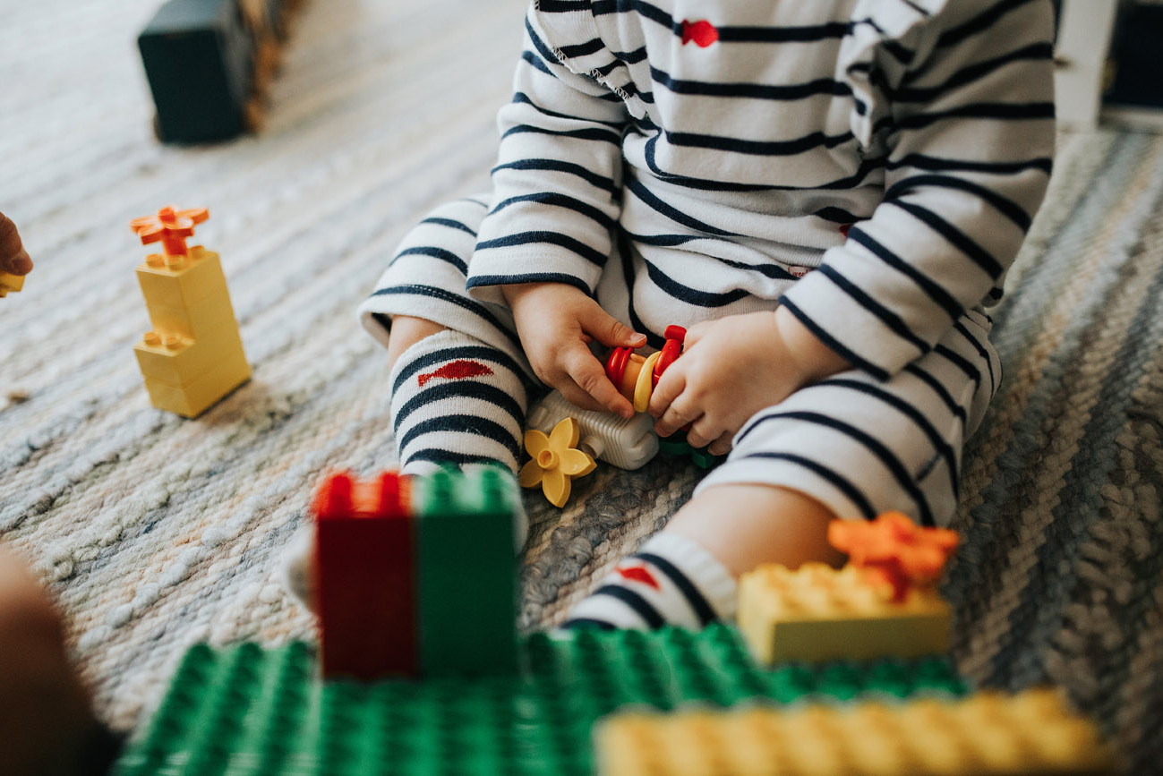 Detail of toddler's hands playing with legos