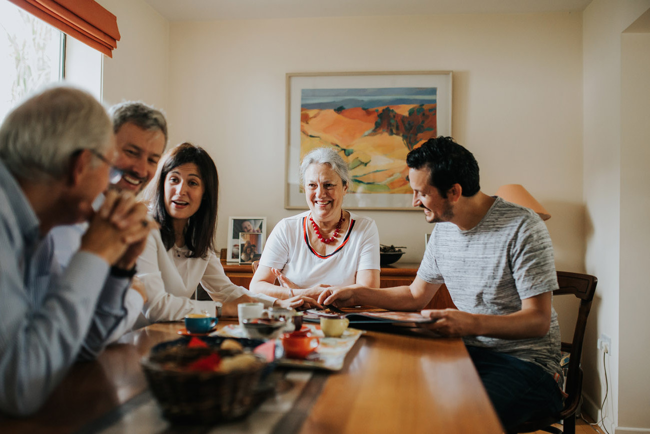 Grandparents and their children chatting and laughing at the table while looking through photo albums