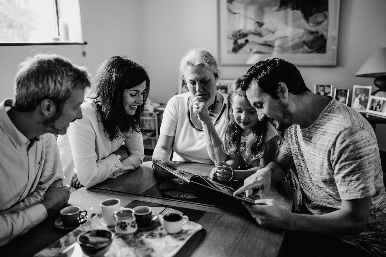 Grandparents, parents and grandchildren sharing a moment together looking through photographs