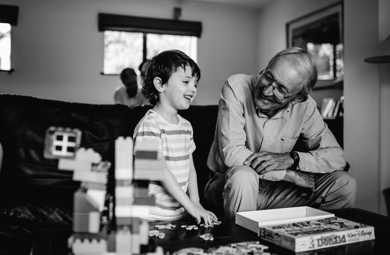 Grandfather and grandson doing a jigsaw and laughing
