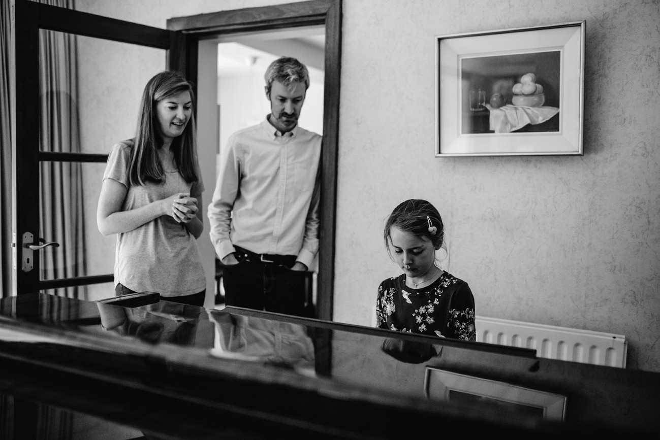 Girl playing piano while her parents are watching her smiling