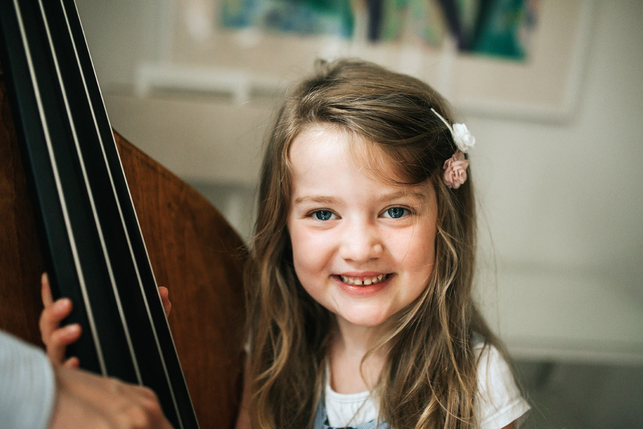 Little girl looking and smiling at the camera beside a music instrument