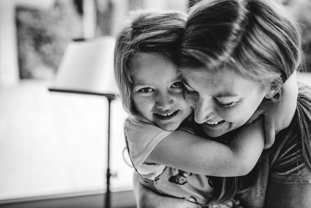 Mother and daughter hug with smiles