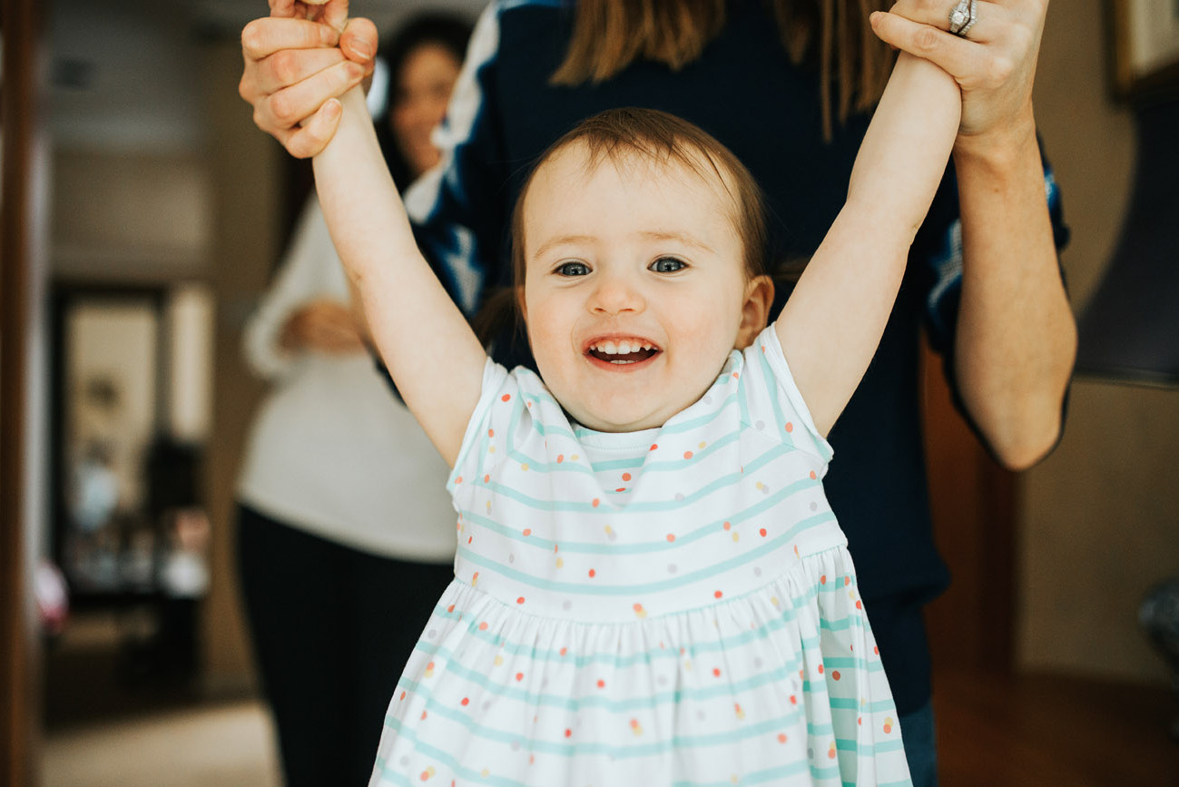 Fun photograph of little girl being lifted and laughing