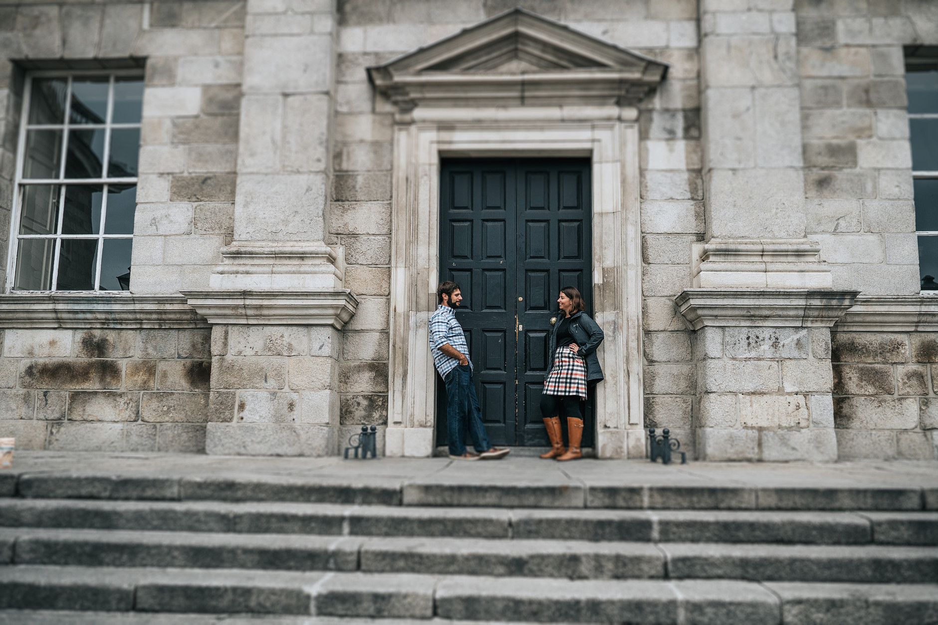 Couple stand up in front of a blue door in Trinity College, Dublin