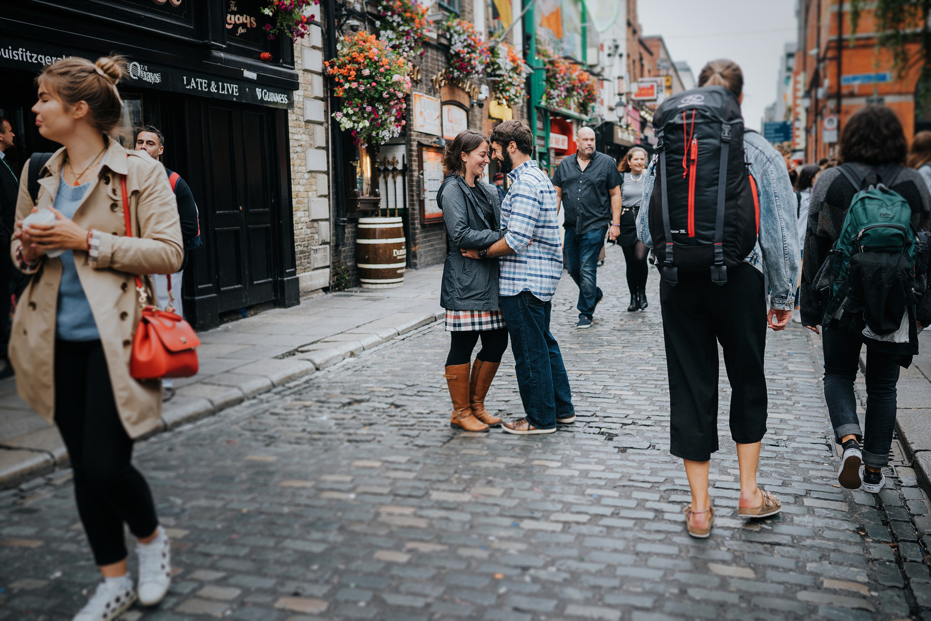 Couple hugging in the middle of the passing by tourists in busy Temple Bar, Dublin