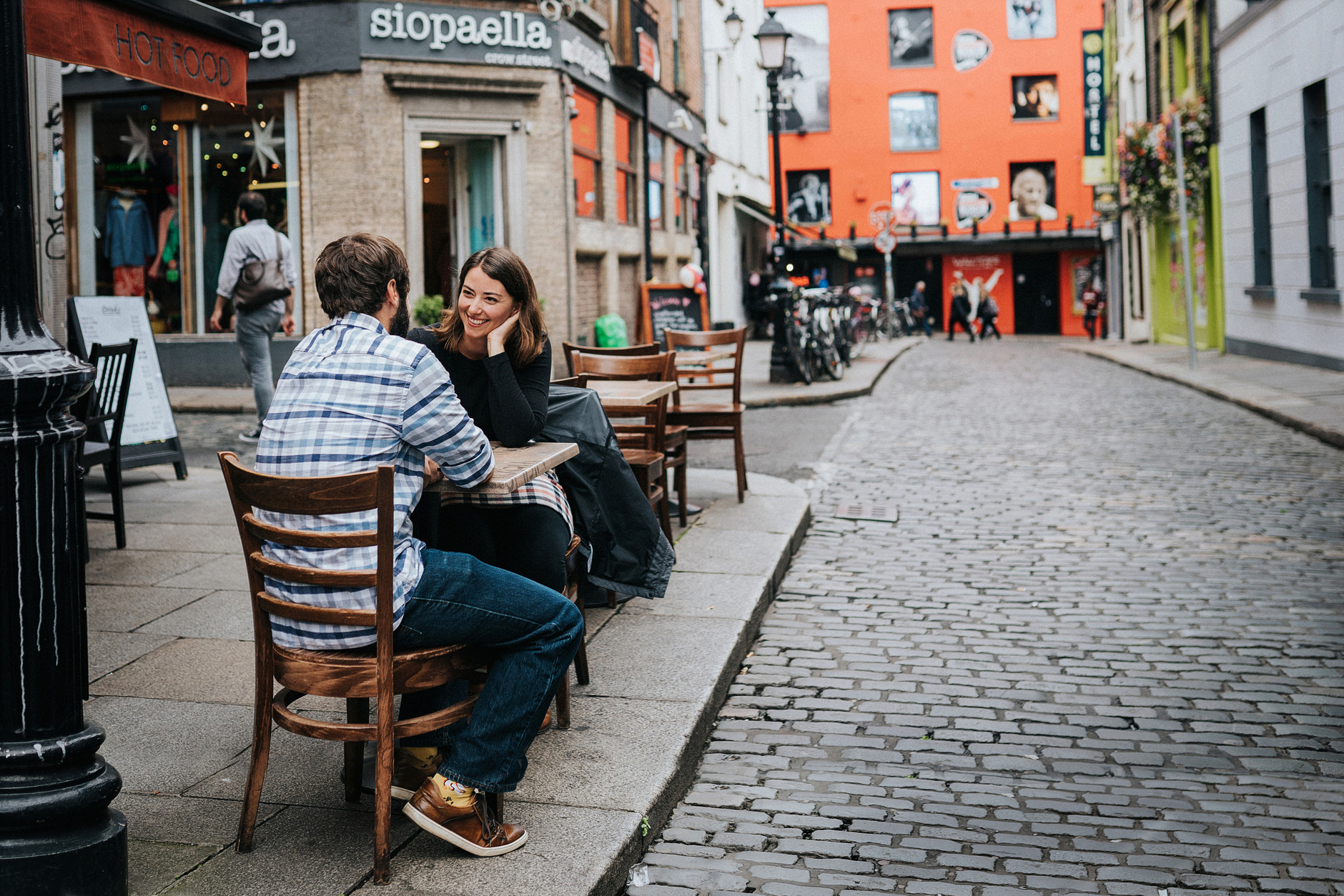 Couple sitting at a table in Temple Bar, with the wall of fame in the background