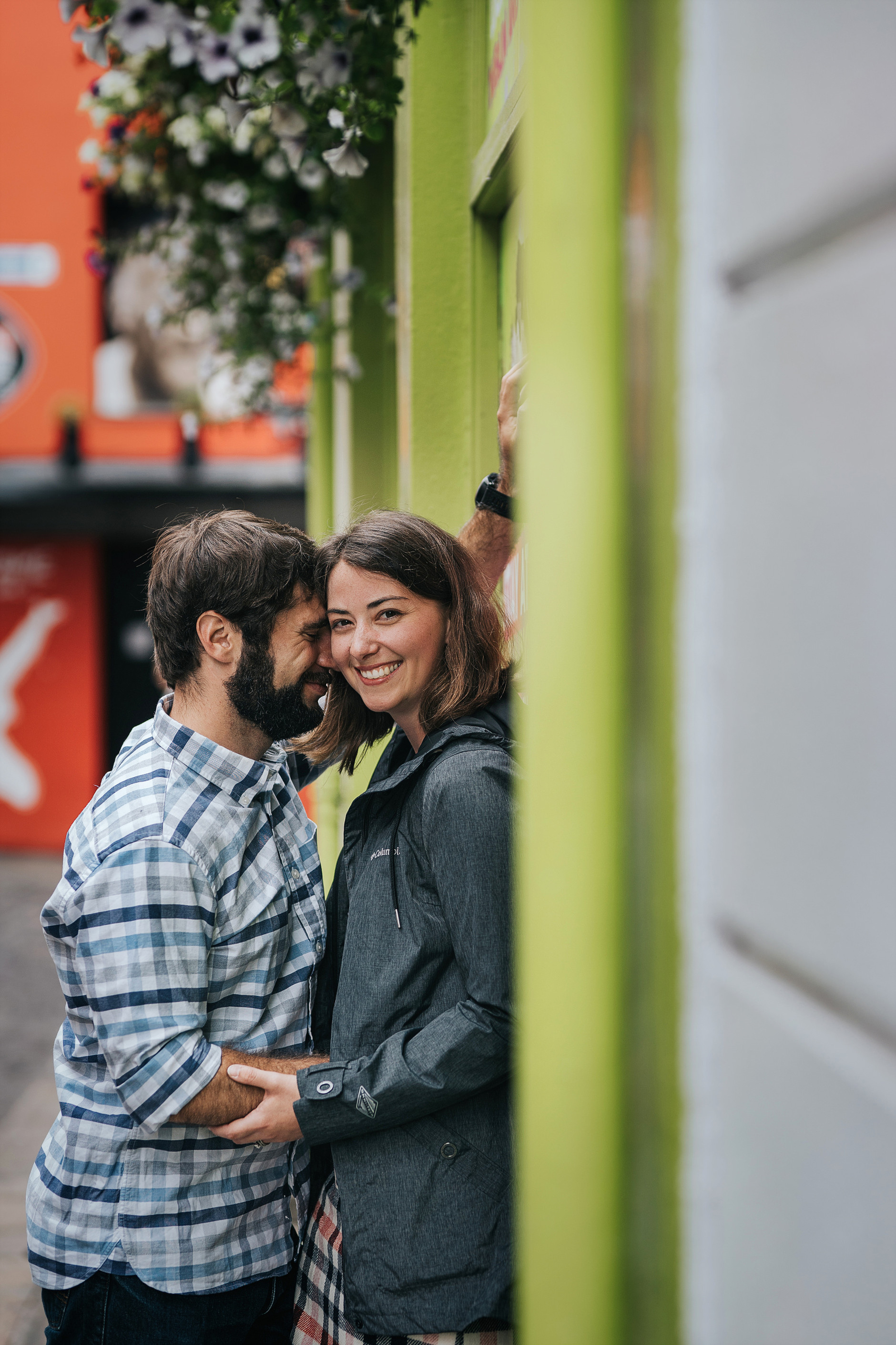 Posed portrait of the couple smiling and hugging in the street of Dublin: love