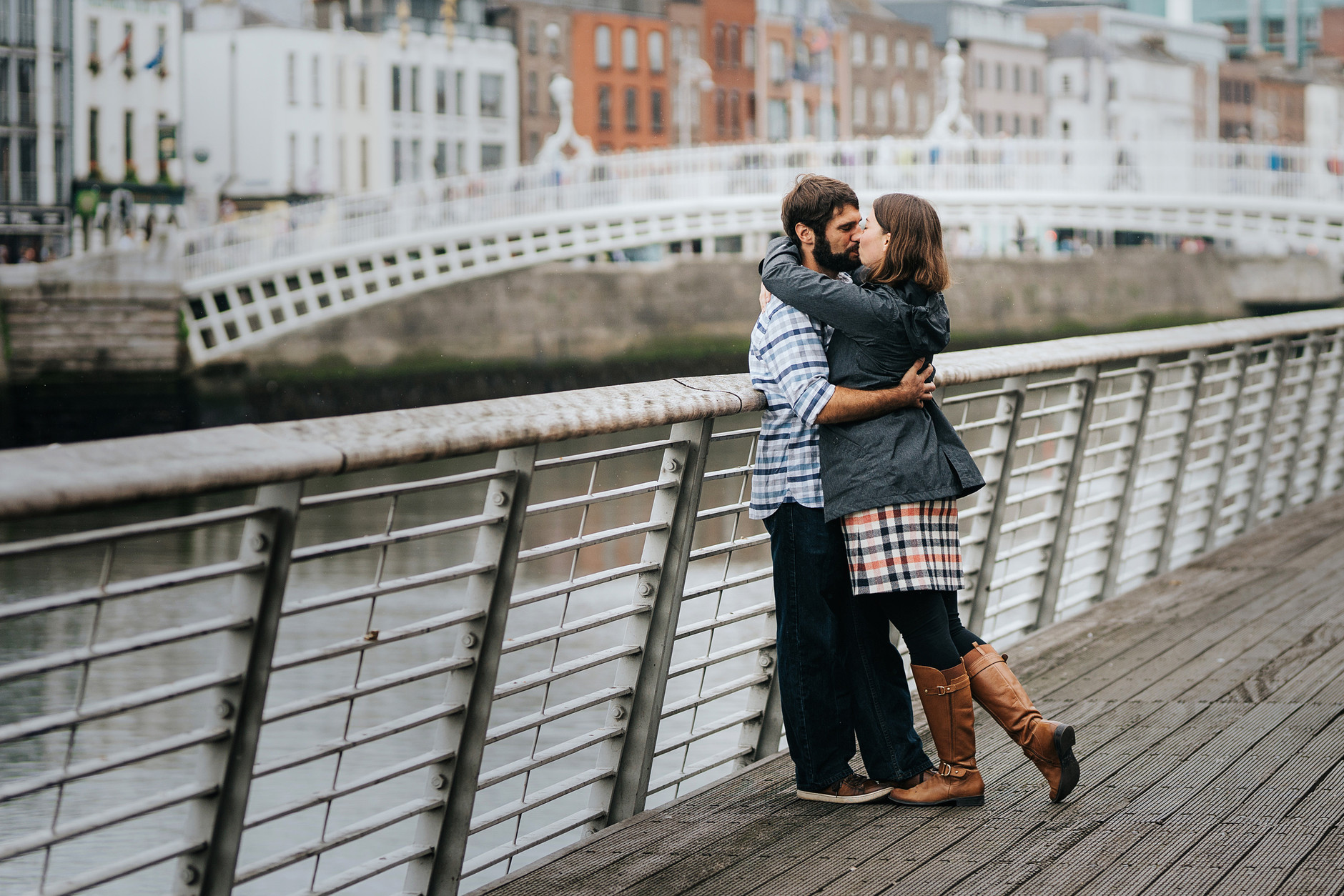 Couple kissing on Bachelors Walk in Dublin in front of the Happeny Bridge