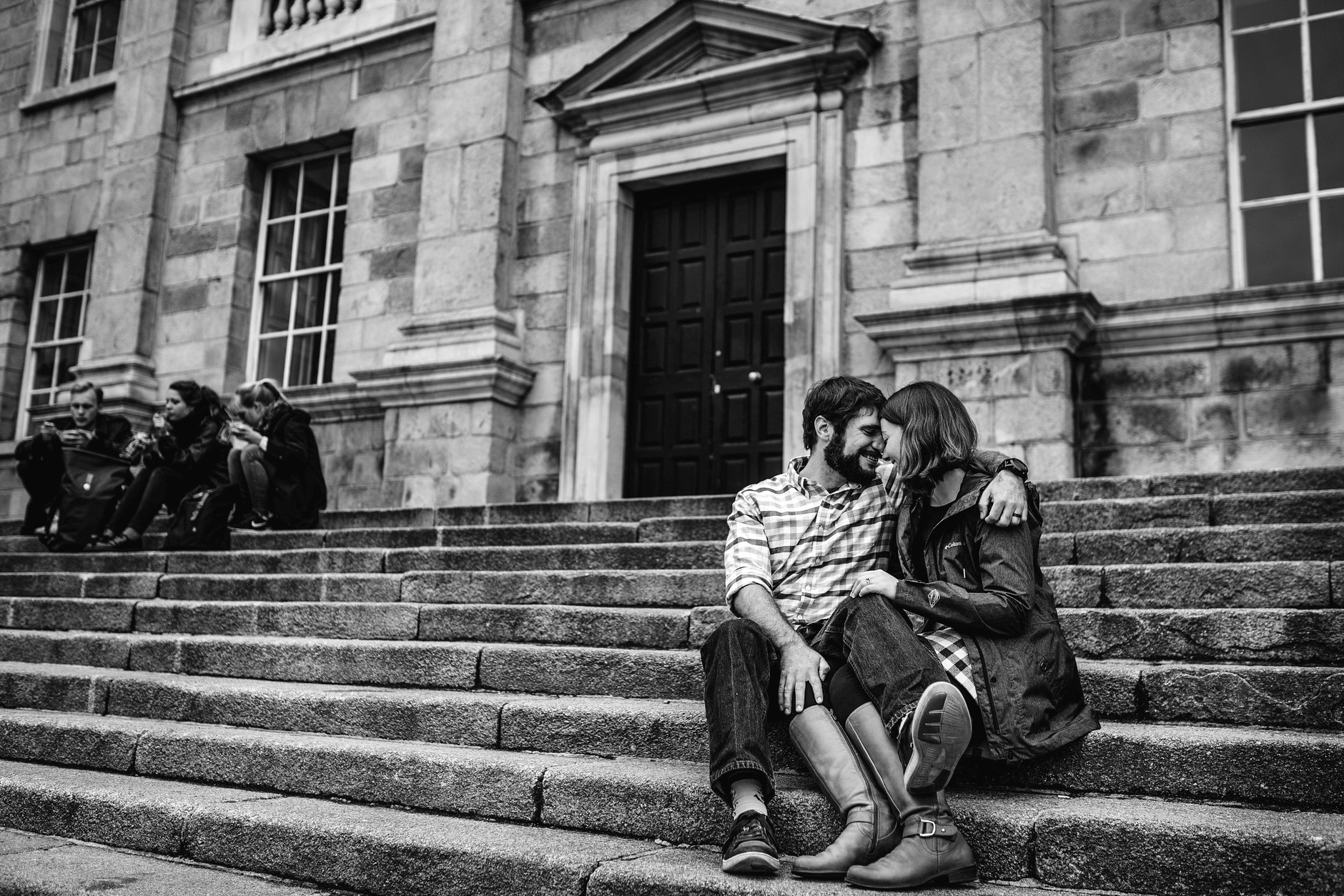Couple sitting on steps in Trinity college, their legs tangled