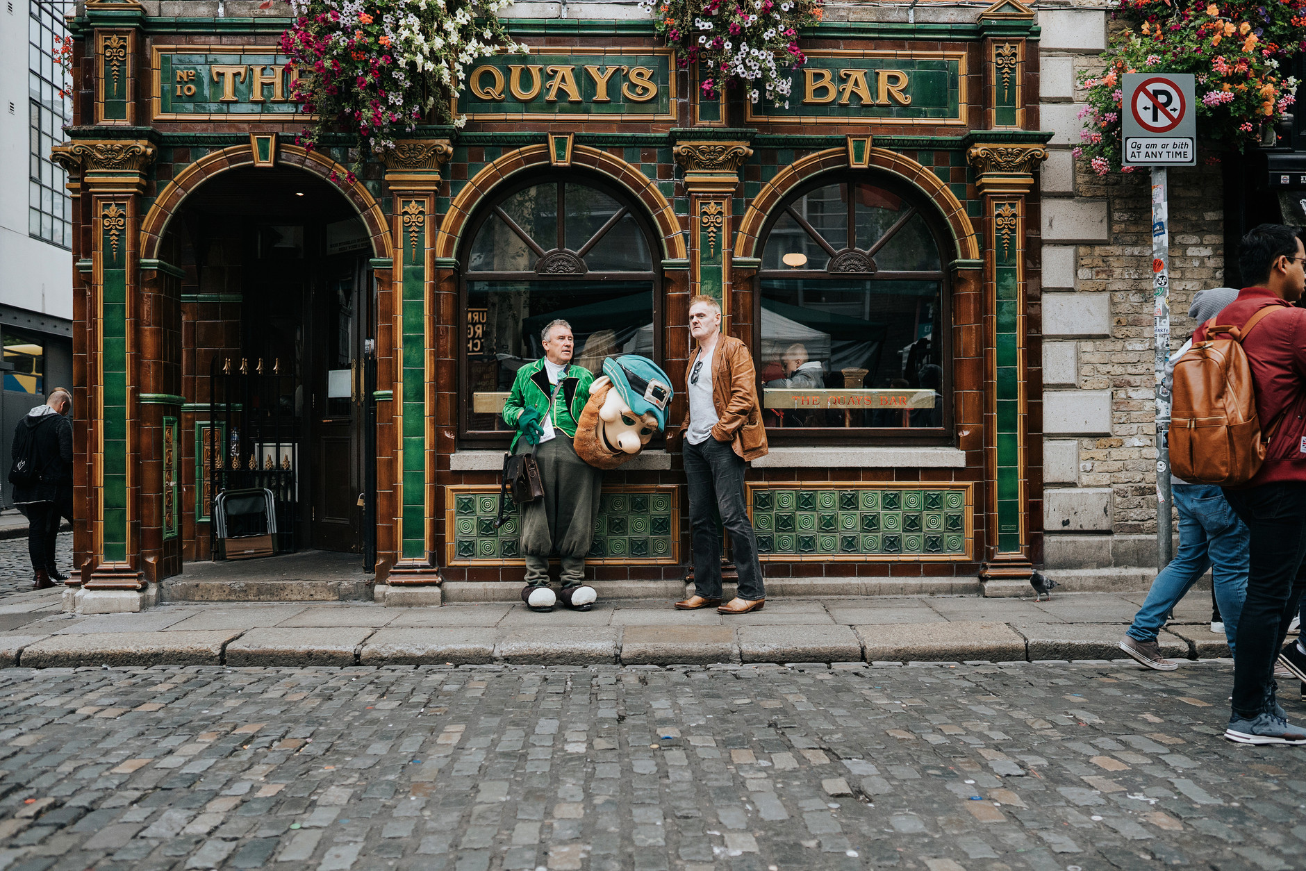Leprechaun chatting with a man in front of Quay's Bar in Temple Bar, Dublin