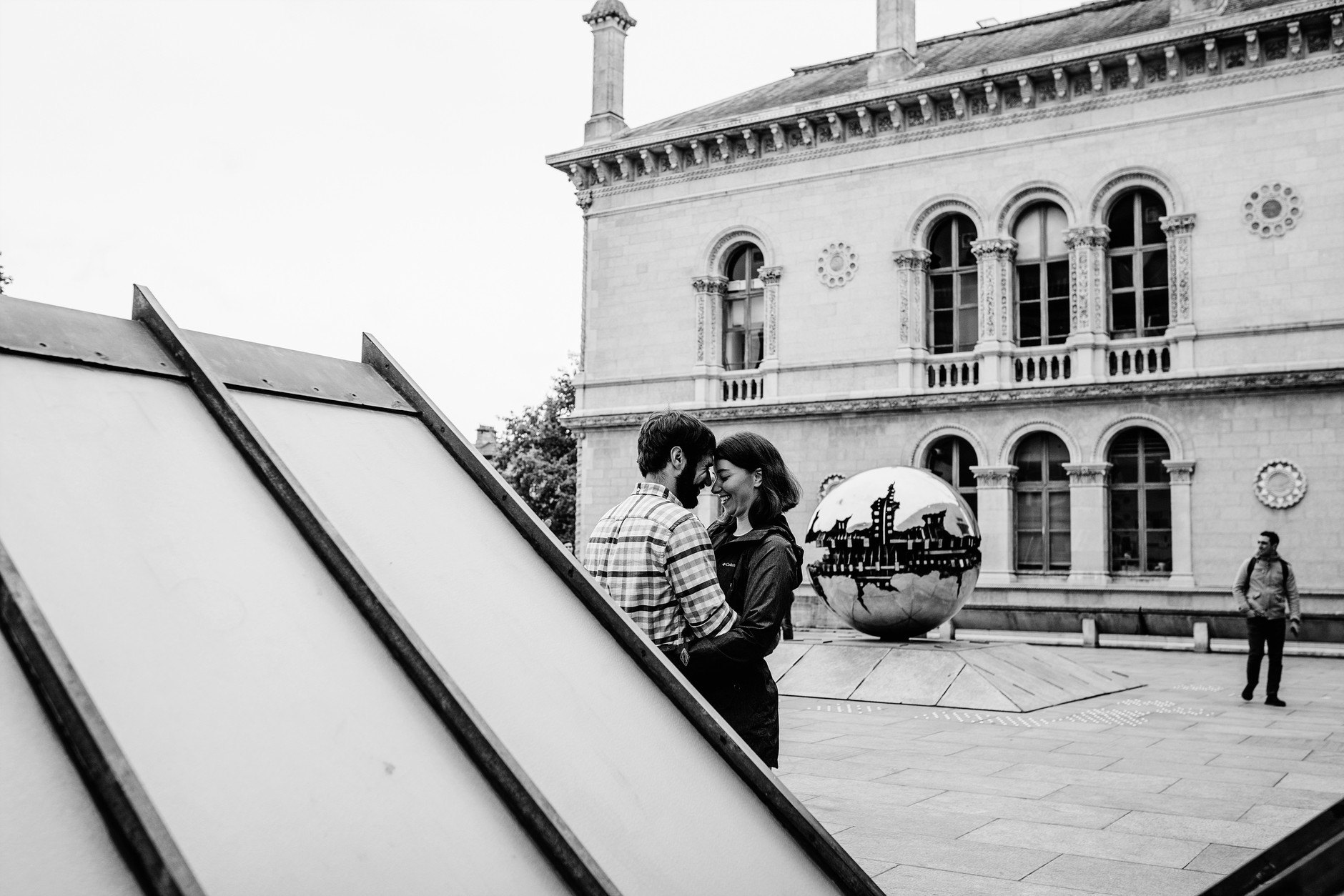 Couple hugging while posing in Trinity college for their vacation photography session