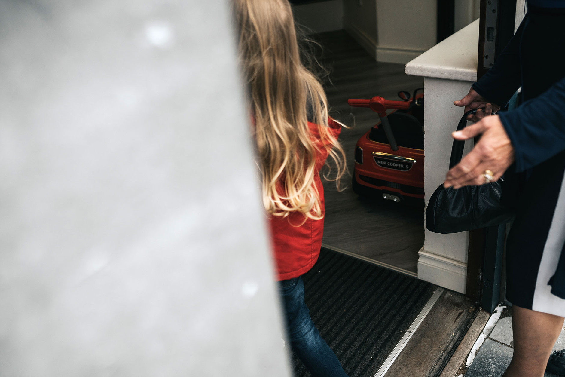 Boy with long blond hair passing the door of the barber