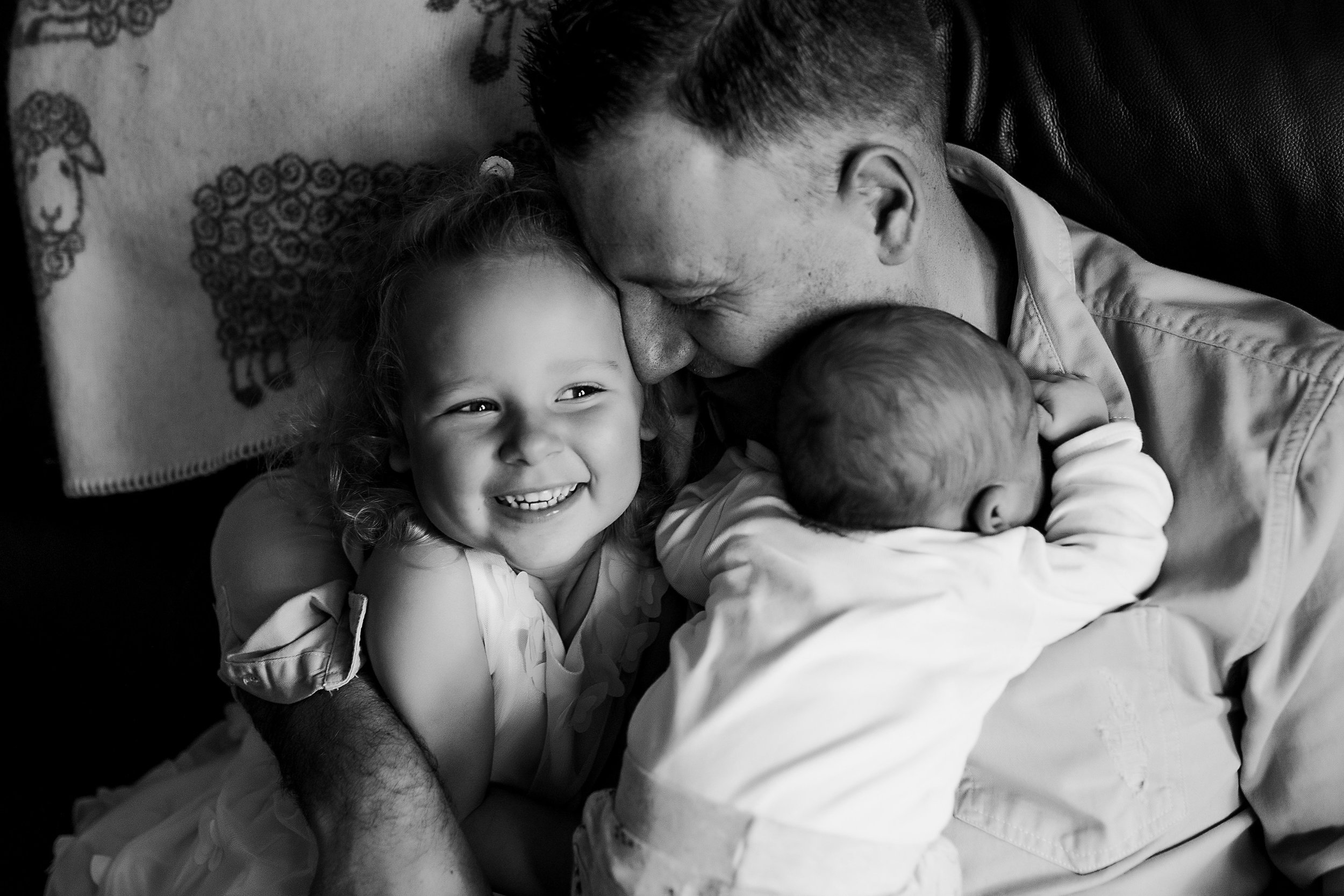 Father hugging his smiling daughter and newborn baby
