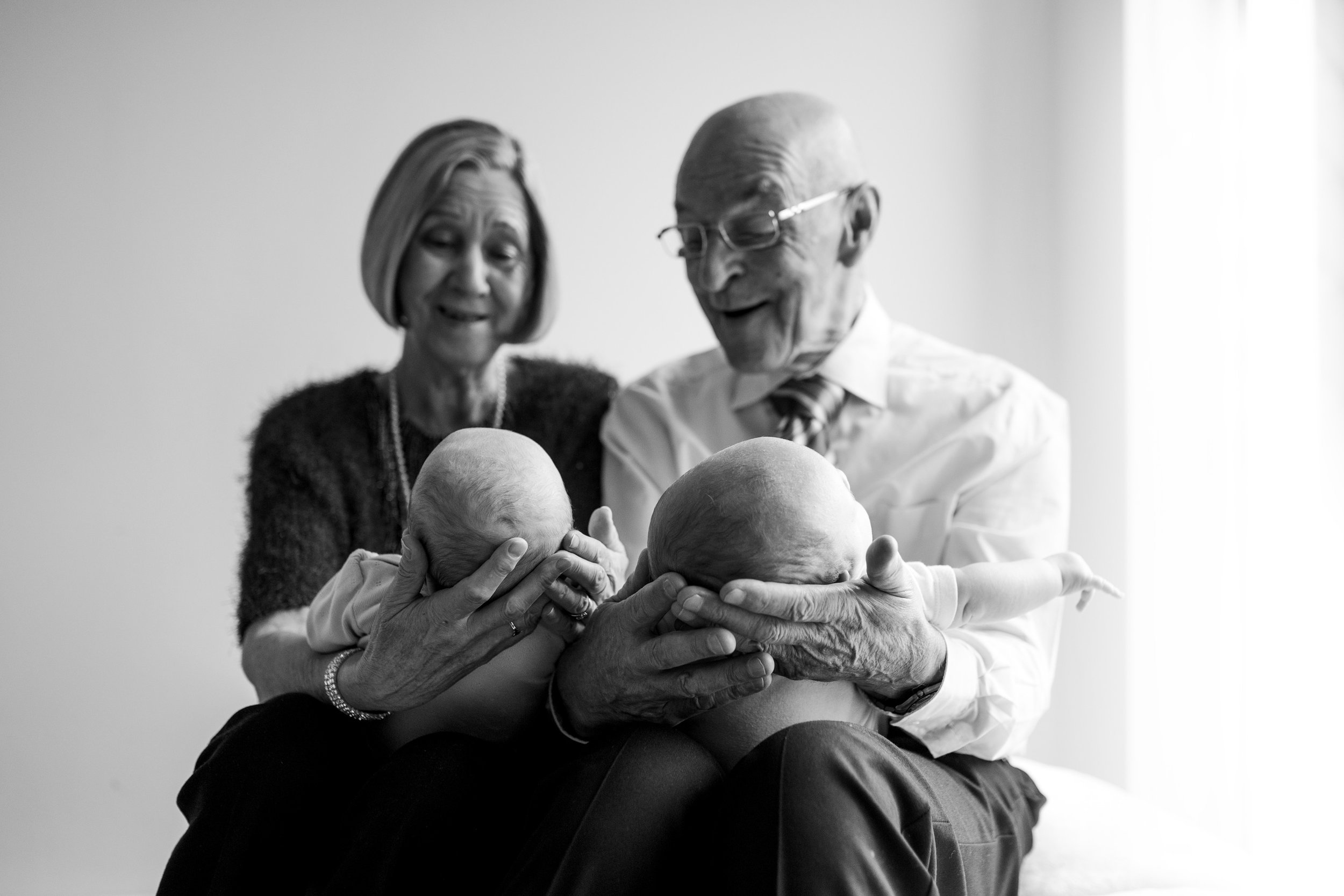 Grandparents holding twin newborn babies and smiling