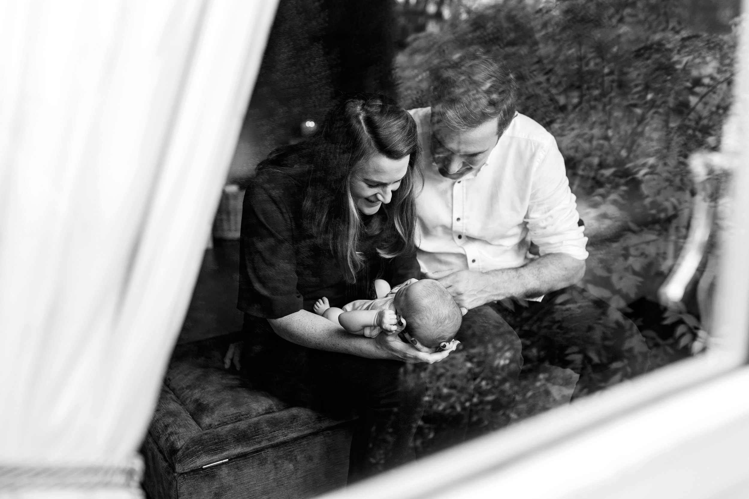 New mother and father holding and looking at their infant seen through the window