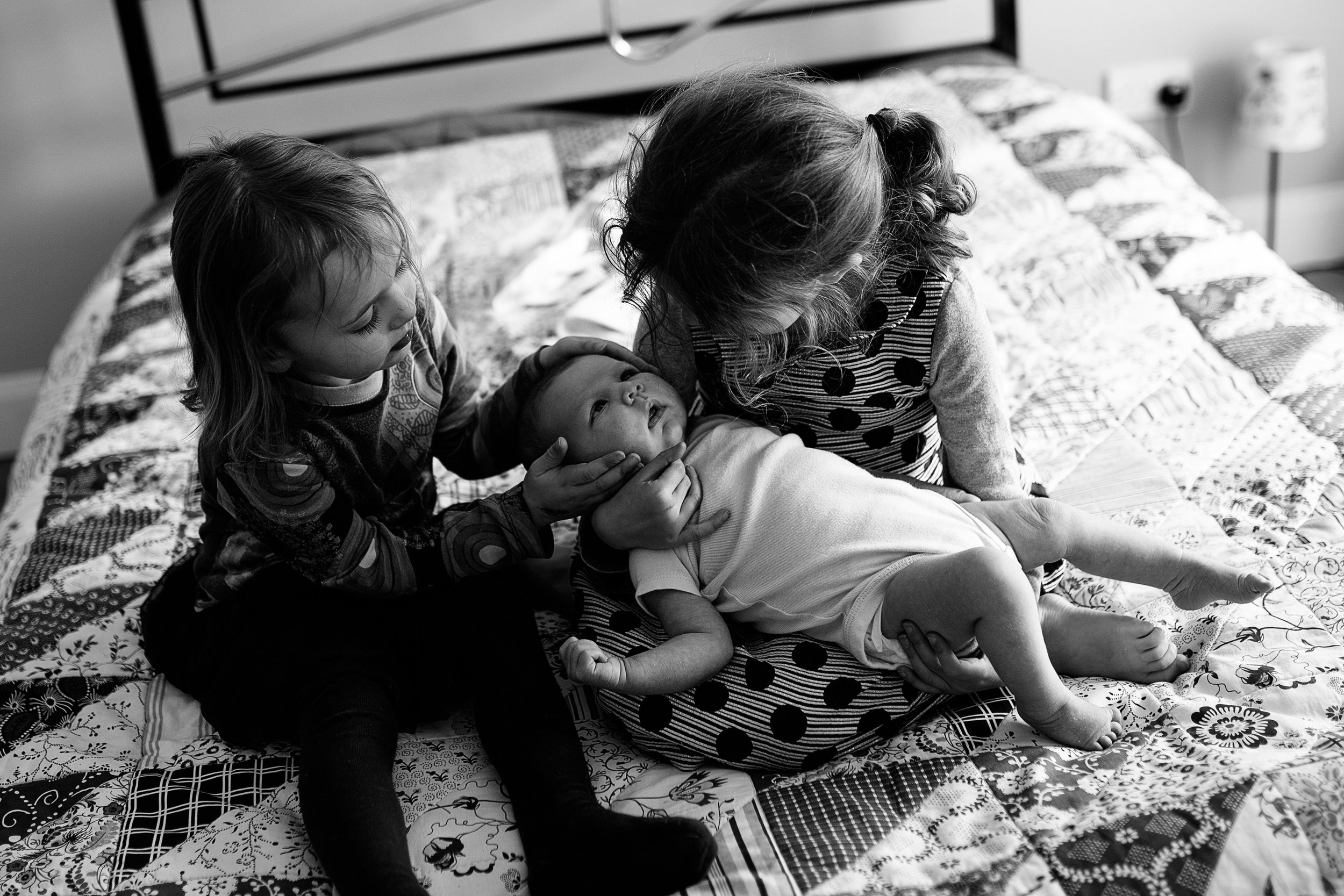 Two sisters looking at their newborn baby on the bed at home