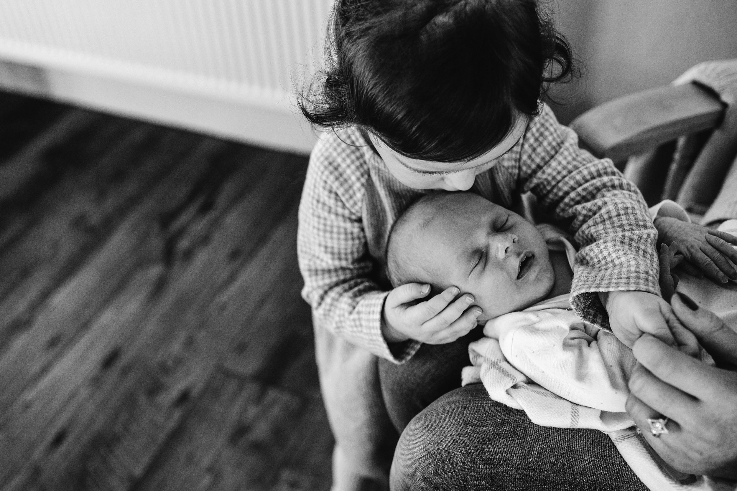 Big sister kissing her baby brother on the head at home
