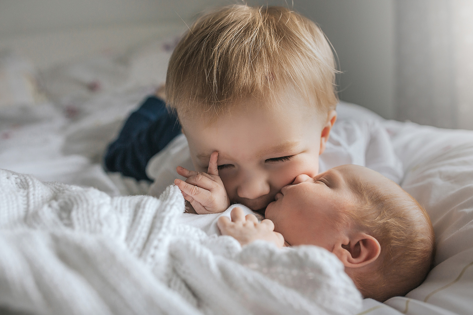 Big brother smiling and kissing his baby brother