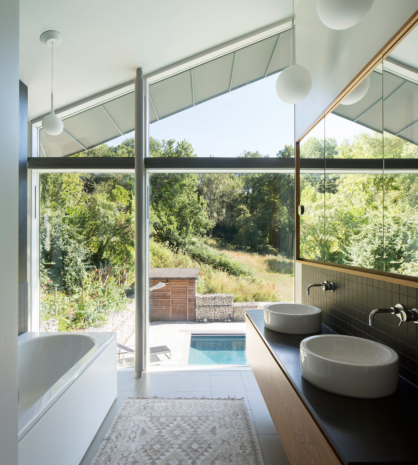 Bathroom of extension and remodelling of large 1970s house Porter Leake House with view of pool