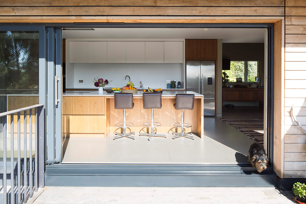 Folding kitchen terrace doors of extension and remodelling of large 1970s house Porter Leake House