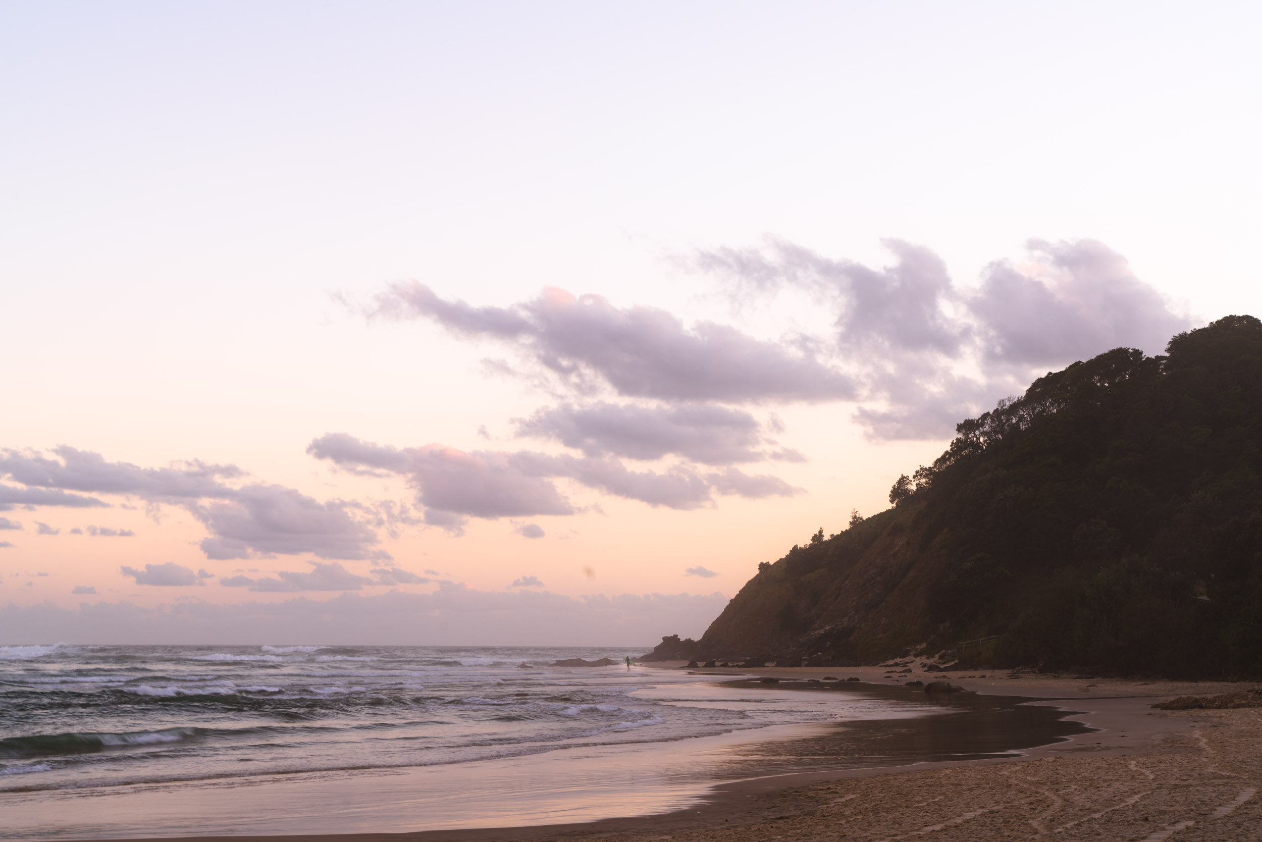 A surfer at sunrise heading out to the break at Wategos Beach.