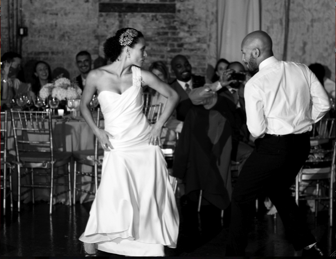 Bride and groom doing a salsa at a wedding with bride shaking her hips