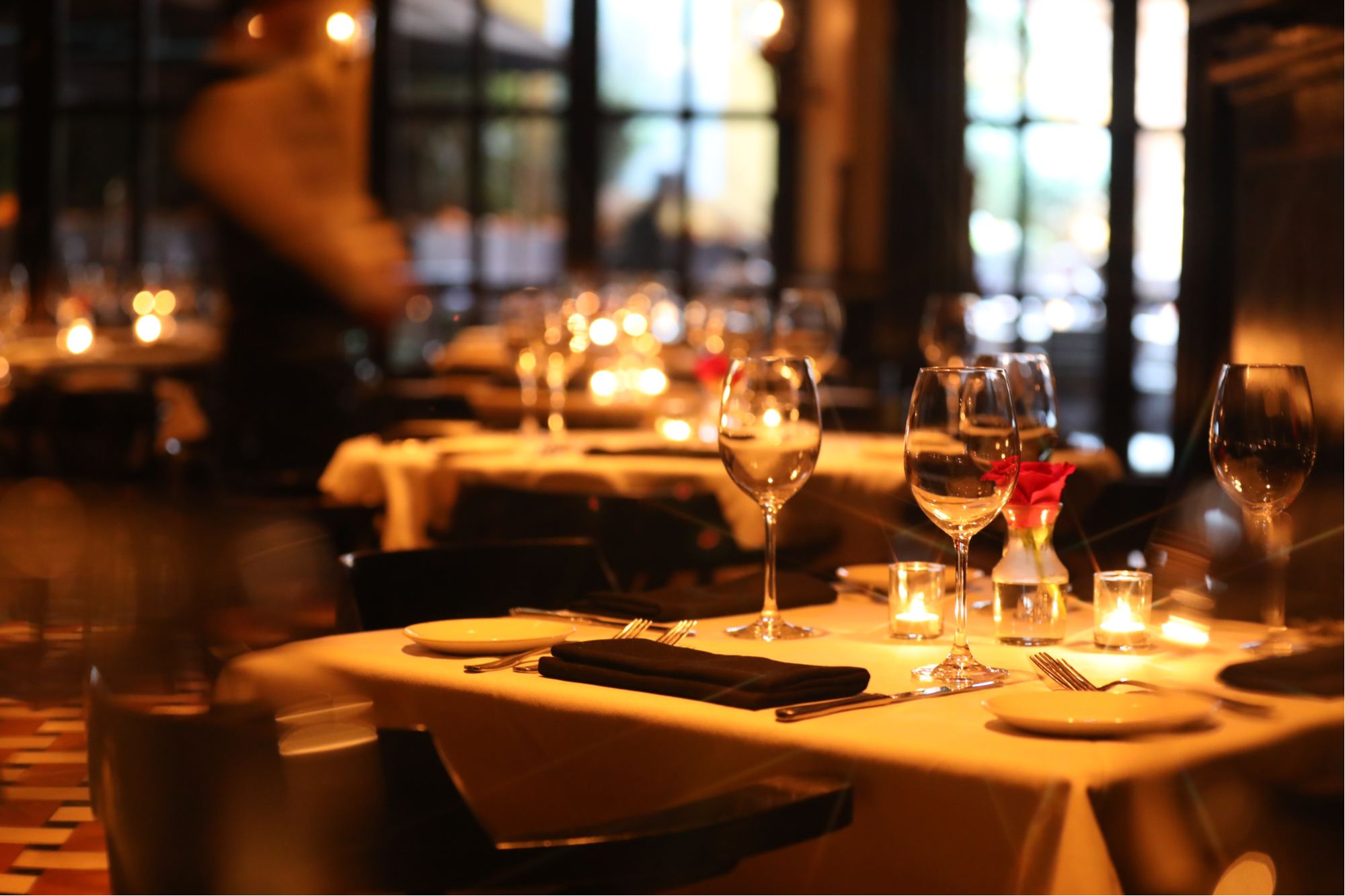 Empty wine glasses, plates, napkins and tea candles on a table at a fine dining restaurant