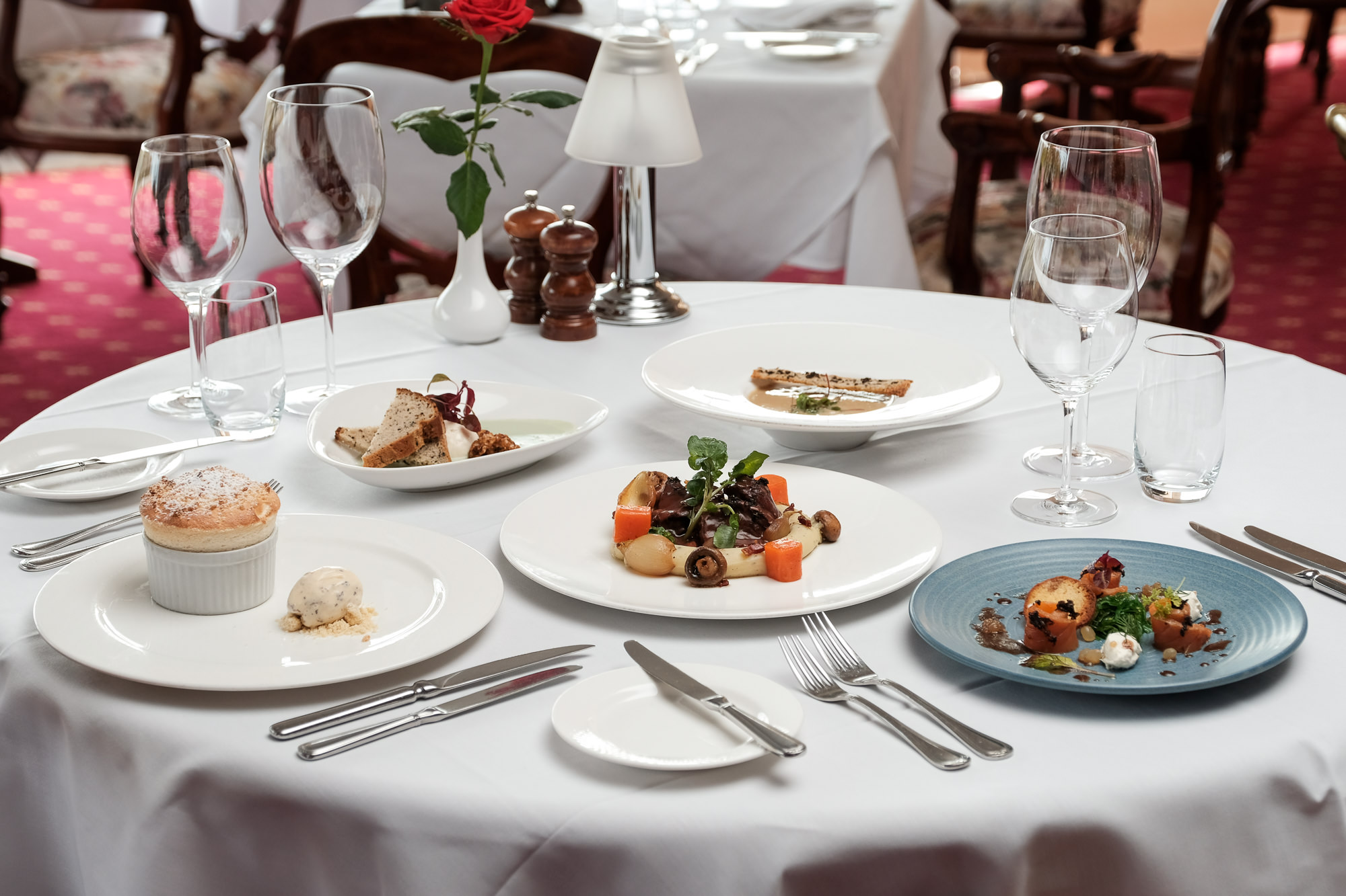 Five plates of fine dining food on a white table with empty wine glasses