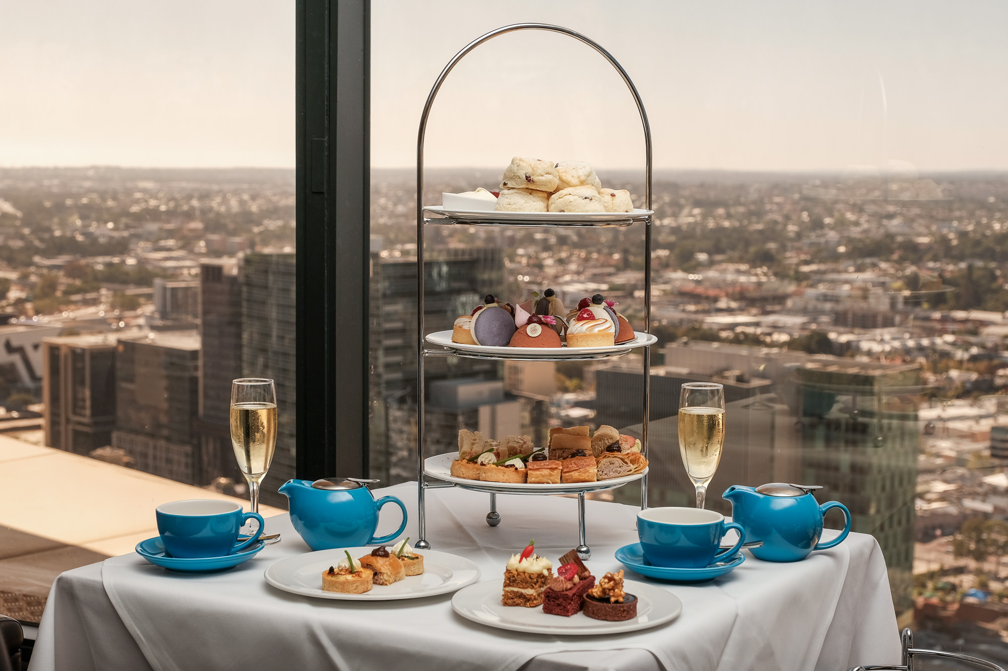 Three-tier high tea with scones, cakes and savoury treats with two glasses of bubbly overlooking Perth