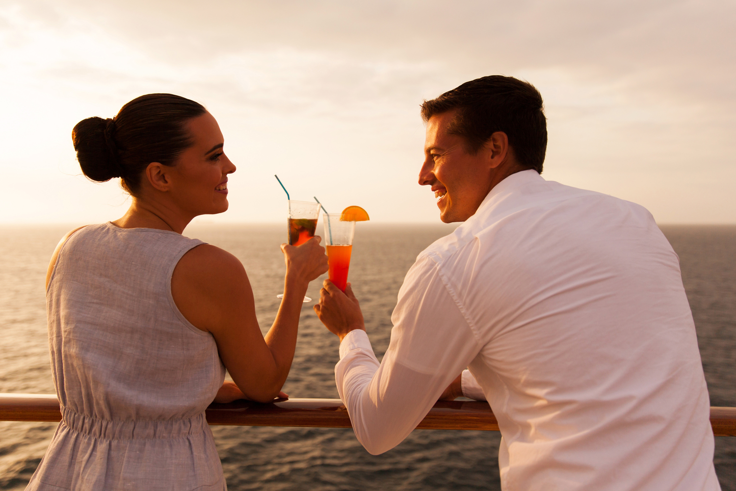 Young couple clinking cocktail glasses while overlooking the ocean onboard a cruise ship
