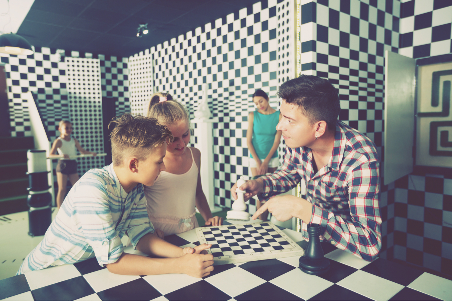Young family huddled over a chessboard in a black and white escape room, trying to solve a puzzle
