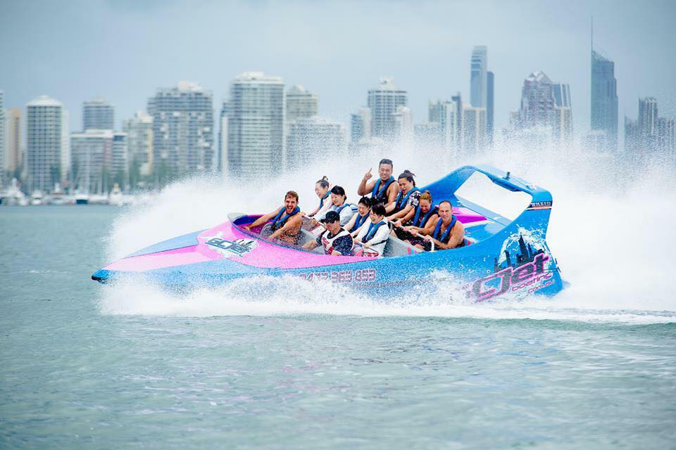 10 people on a high-speed jet boat, speeding through the water with the Gold Coast skyline in the background