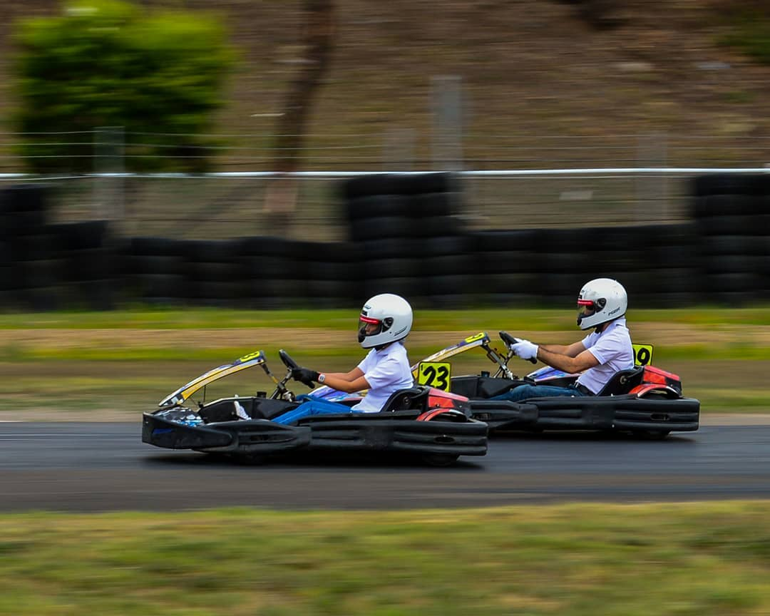 Two people driving go-karts with a blurred background