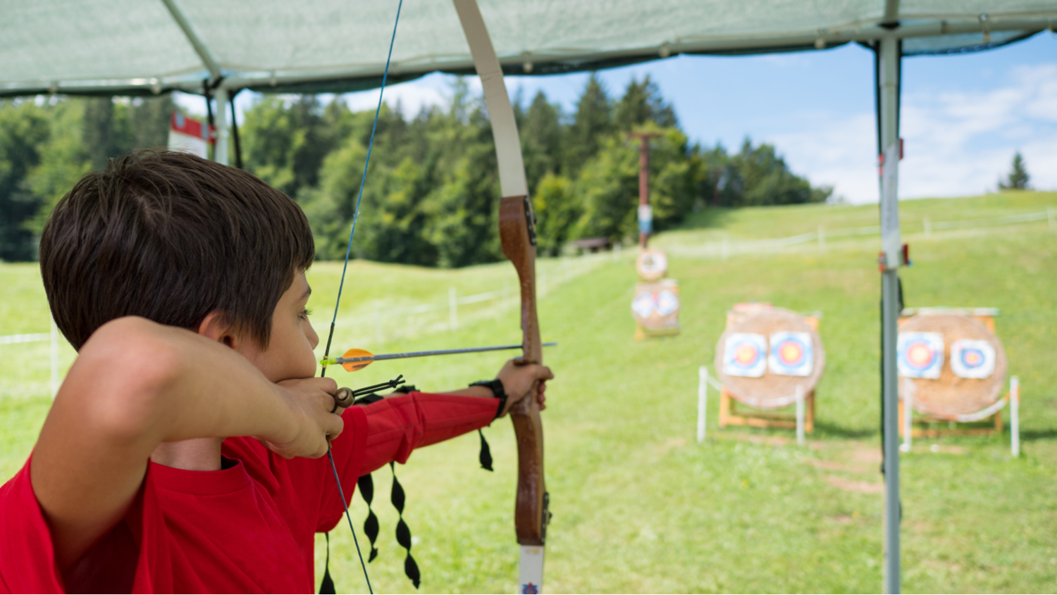 A young boy preparing to shoot a target with a bow and arrow