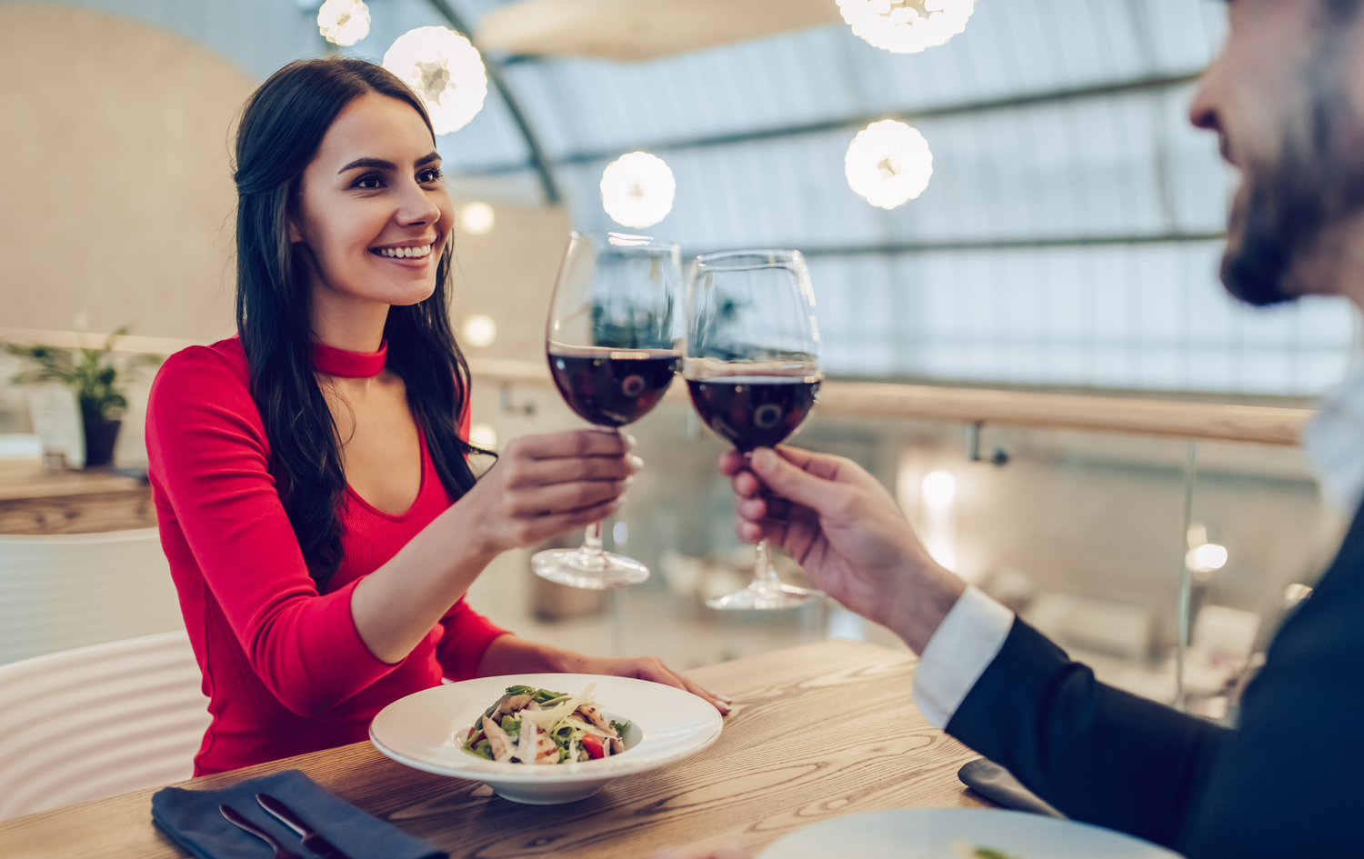 A young brunette woman in red and her male date clinking glasses of red wine at a fine dining restaurant