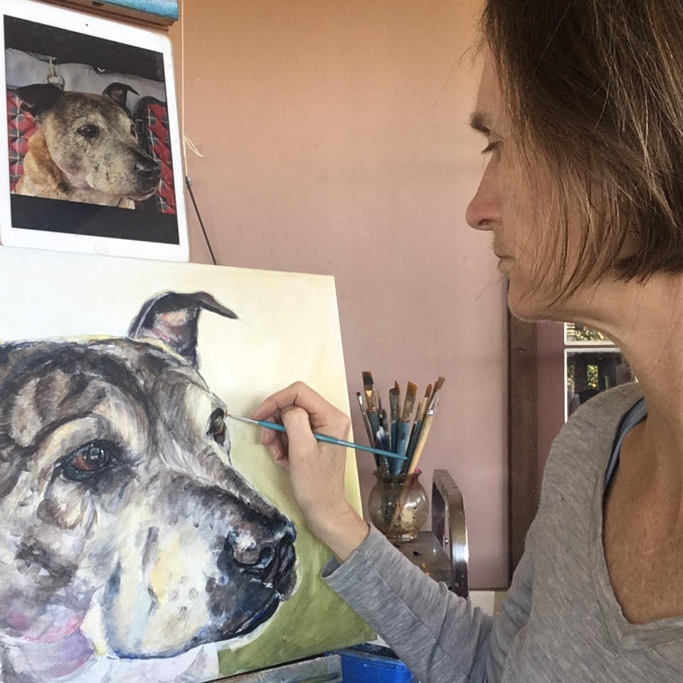 Opal Pastro painting a custom dog portrait of frank the Staffy with reference photo on her IPad.