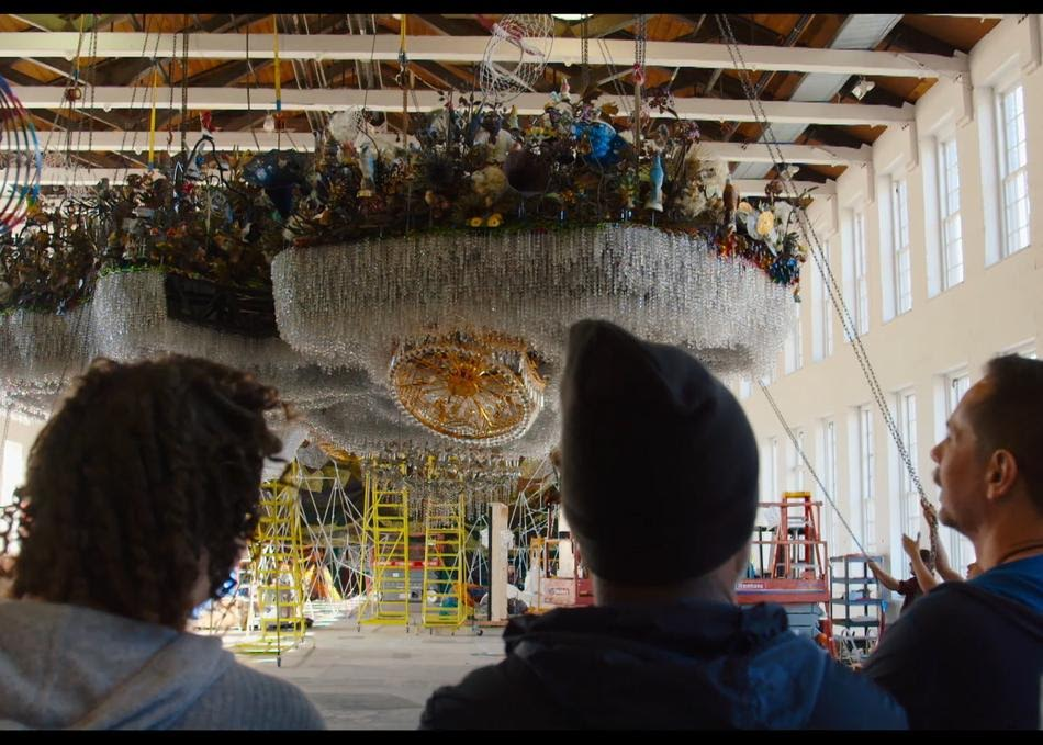 """Artist Nick Cave and curator Denise Markonish watch as Cave's """"CLOUD"""" is lifted up in MASS MoCA Building 5"""