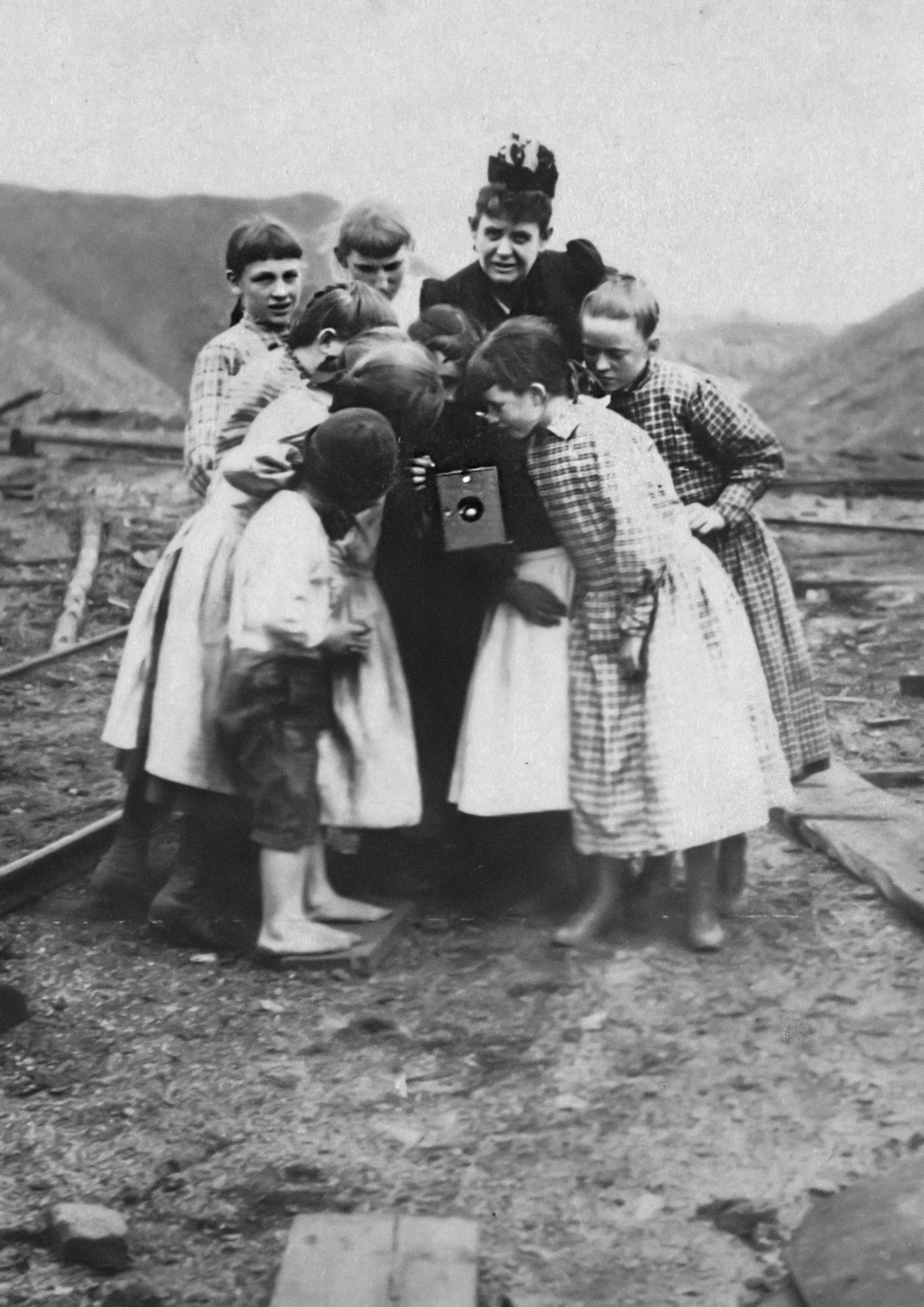 Frances Benjamin Johnston with group of children looking at her camera