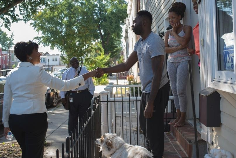 Mayor Bowser greeting a resident outside their home.  (Credit: Office of the Deputy Mayor for Planning and Economic Development)