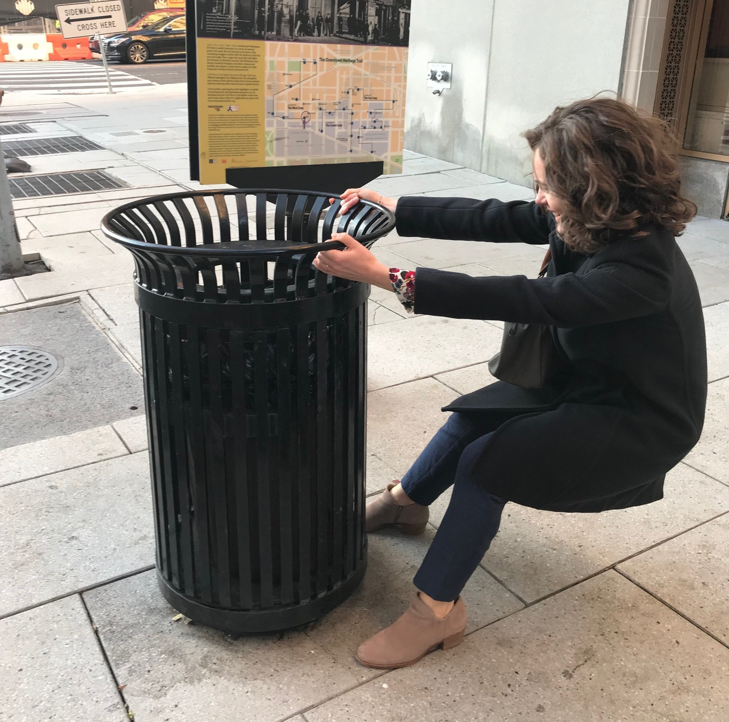 Senior Operations Analyst, Karissa Minnich, tugs on a city trash can for the Smartcans project to see if it's bolted to the sidewalk. It is. (Credit: The Lab @ DC)