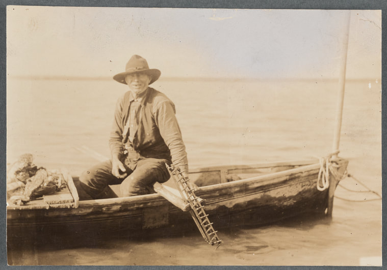 An oysterman sits in a boat with his tongs and other oystering tools. New York Public Library Digital Collections.