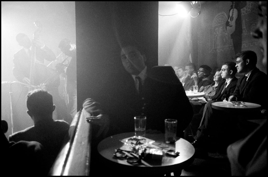 Patrons at the Village Vanguard in 1958, with Miles Davis on stage at the far left (Photo: Dennis Stock/Magnum Photos)