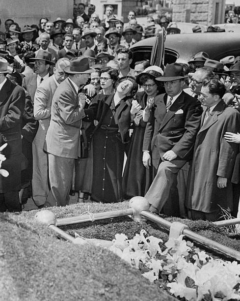 The wife of slain garment district worker William Lurye breaks down at his funeral in the Carmel Cemetery in Cypress Hills, Queens. She is supported by David Dubinsky, President of the International Ladies Garment Workers Union. (Photo by George Torrie/NY Daily News Archive via Getty Images)