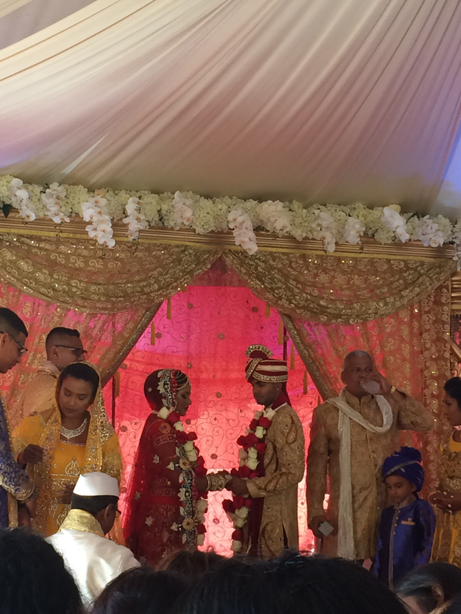 A photo of the Hindu wedding that the author attended. In the center is the bride and groom wearing traditional Indian garb for a Hindu wedding. To the left, the bride is wearing a saree and a veil. To the right, the groom is wearing a kurta and a safa. To the right of the groom, the groom's father is wearing a more traditional kurta, with a scarf, but without the safa.